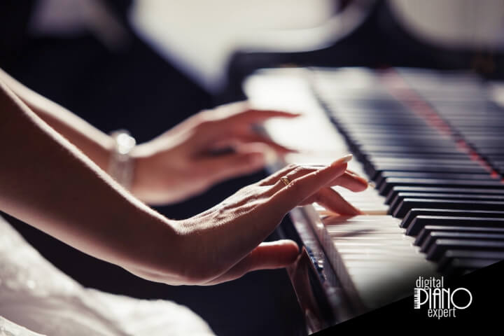 woman playing the piano using both hands