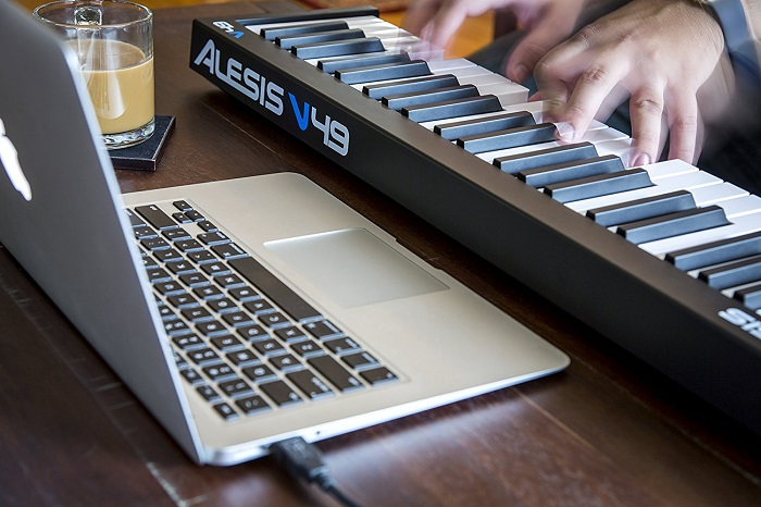 man playing on the Alesis V49 piano with a laptop in front of him