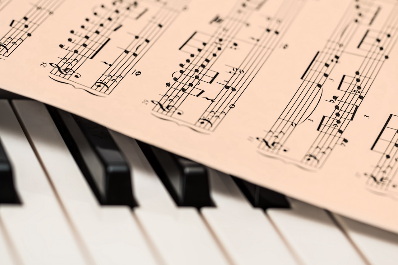 sheet music on top of piano keyboard