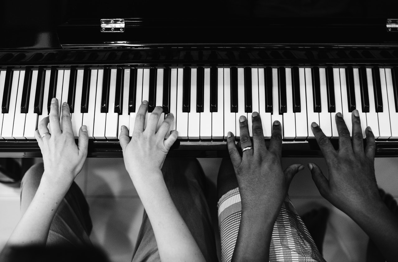 black and white photo of two hands playing the piano