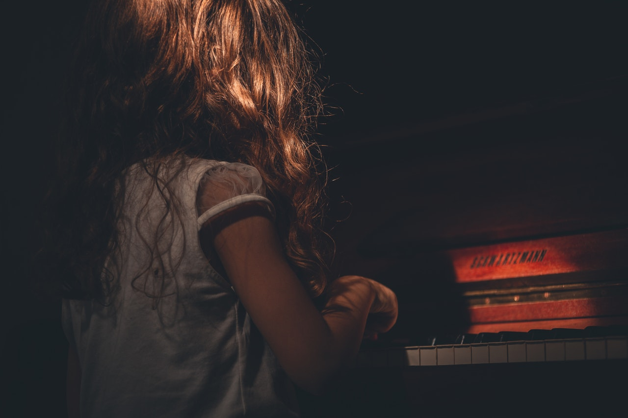 brunette little girl playing the piano