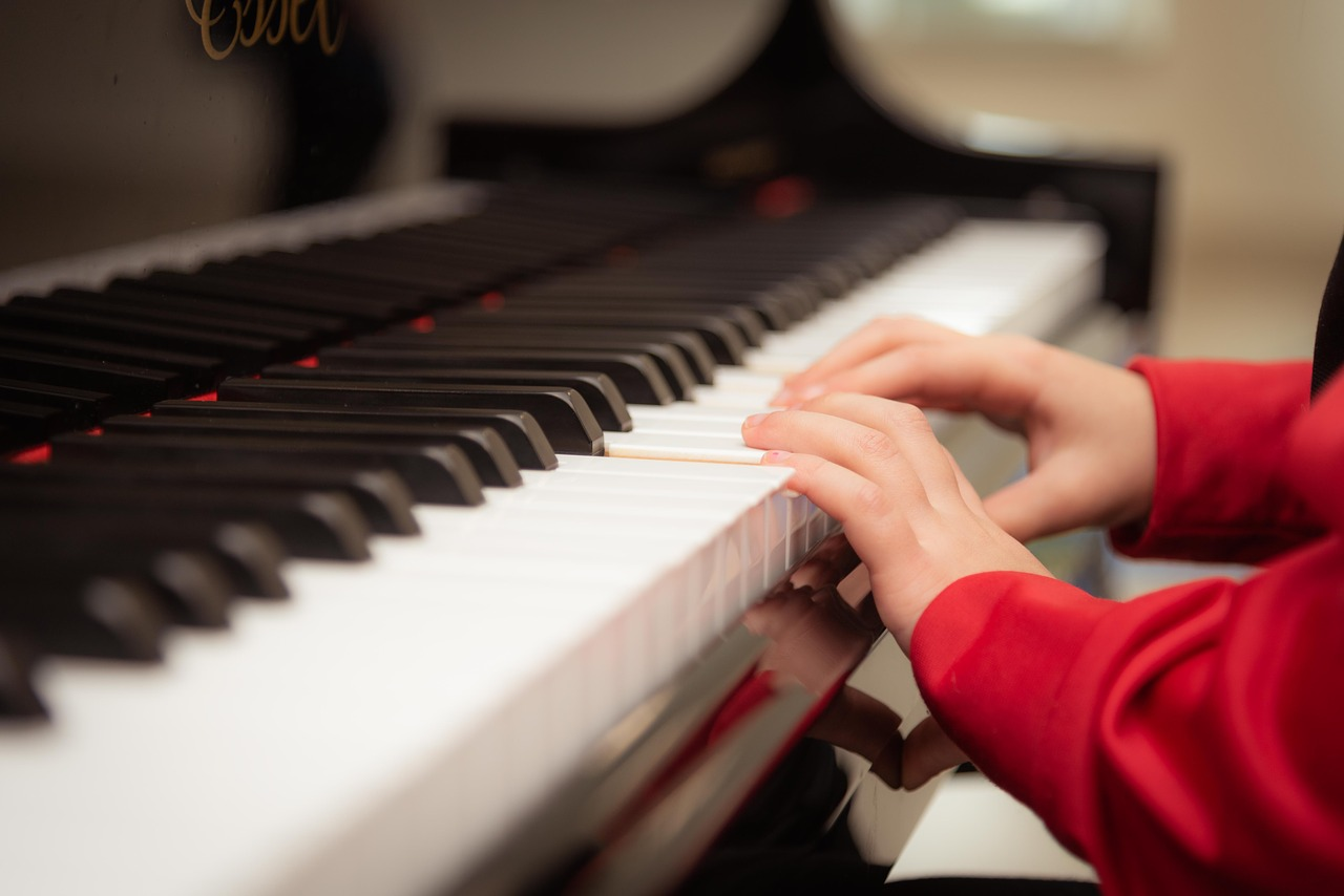 kid wearing red sweater playing the piano