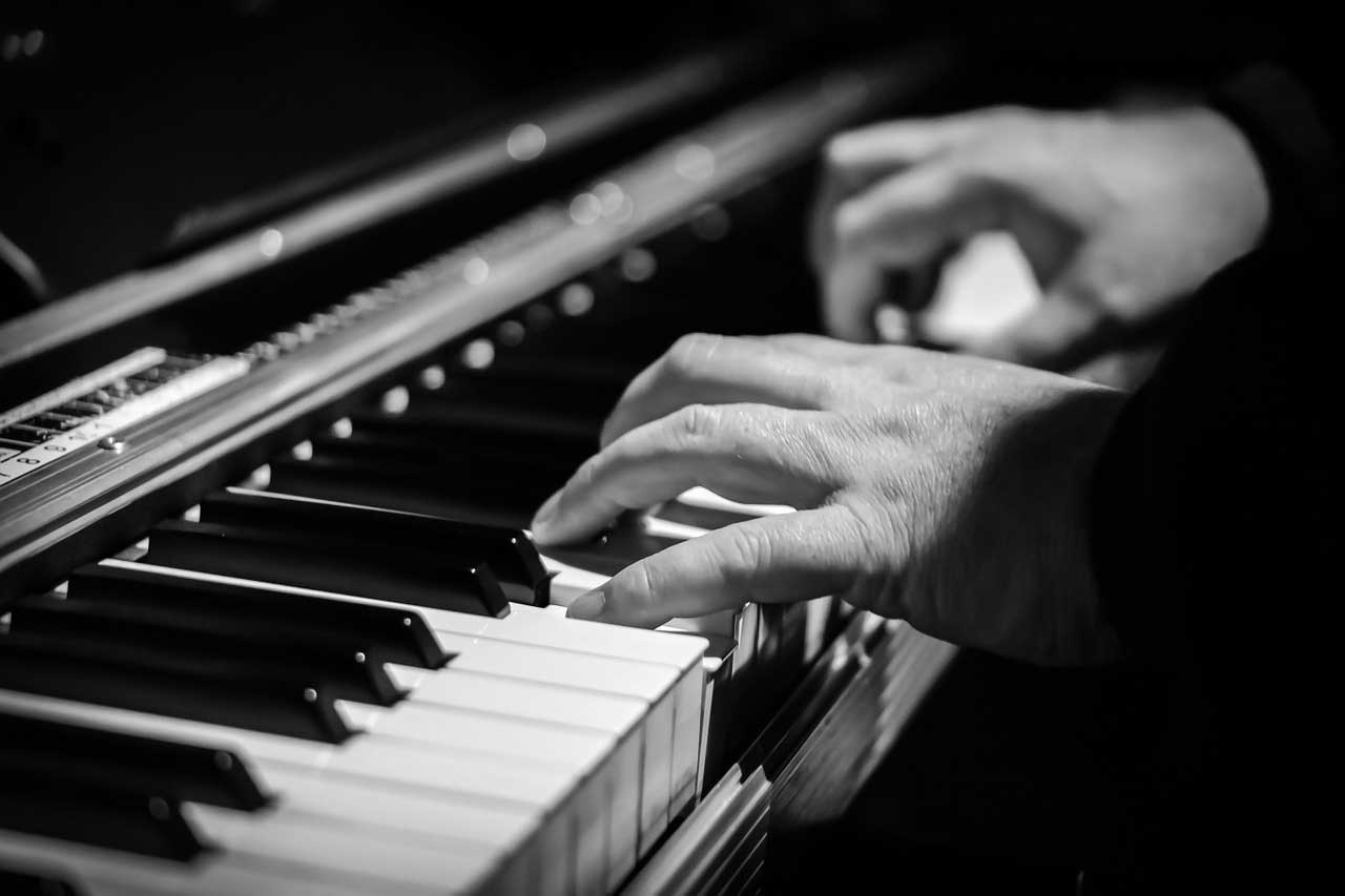 greyscale of a person playing the piano